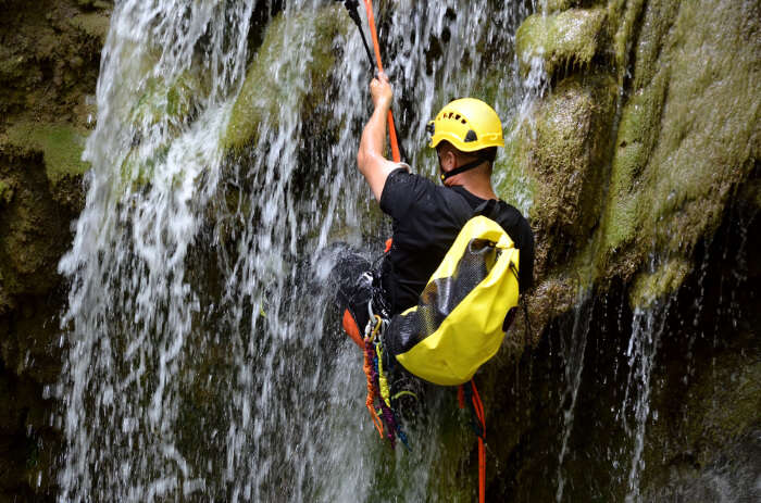 A man rappelling down a waterfall