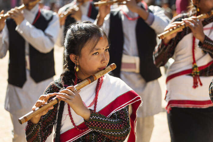 A girl playing Dashain music on flute