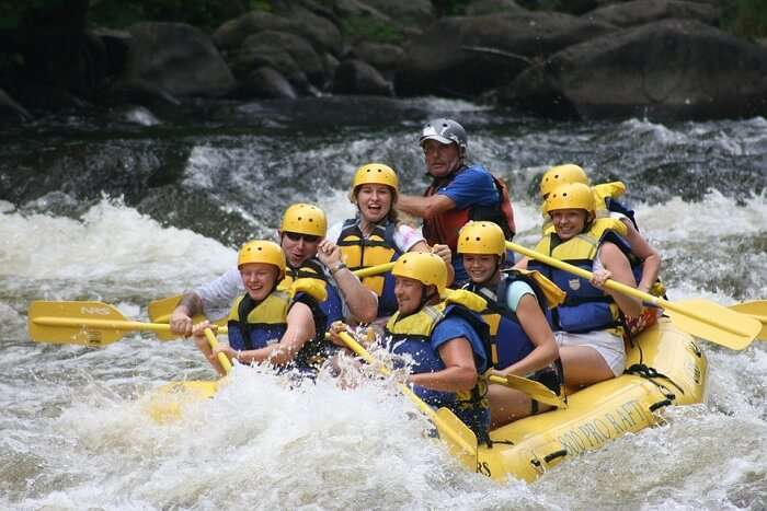 people rafting on a rapid stream