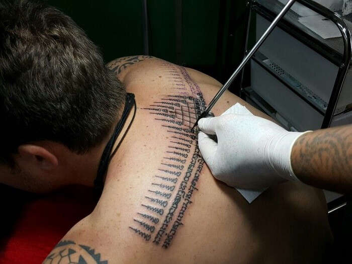 man getting a tattoo on his back