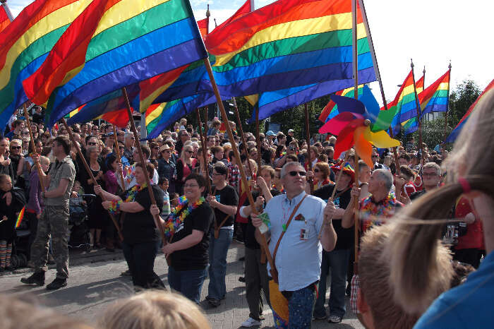 People holding pride flags during a pride parade on streets