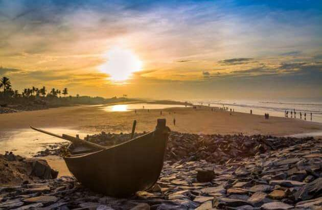 Wooden_boat_on_the_beach_rocks_at_sunrise_with_vibrant_moody_sky_687x478