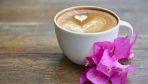 Coffee on a table with pink flower petals