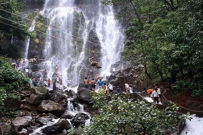 people doing activities near waterfall