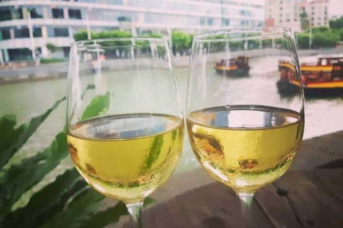 glasses of wine with singapore river in background