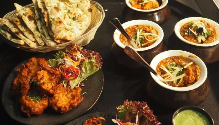 multiple Indian dishes served on table