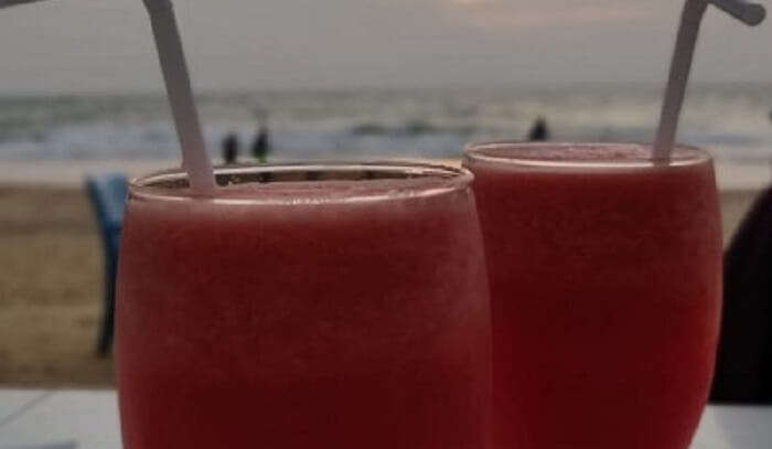 having refreshing drink on the beach