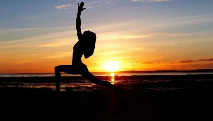 Woman in yoga pose with sunset in the backdrop