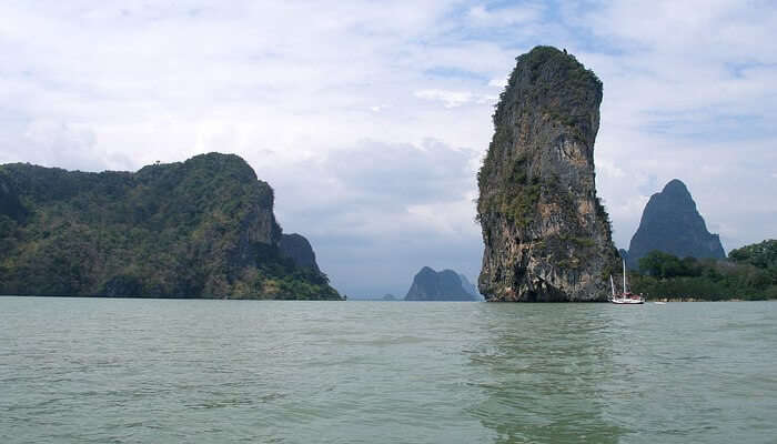 A couple relaxes on a beach in the Phang Nga Bay on one of the best islands to visit in Thailand for honeymoon