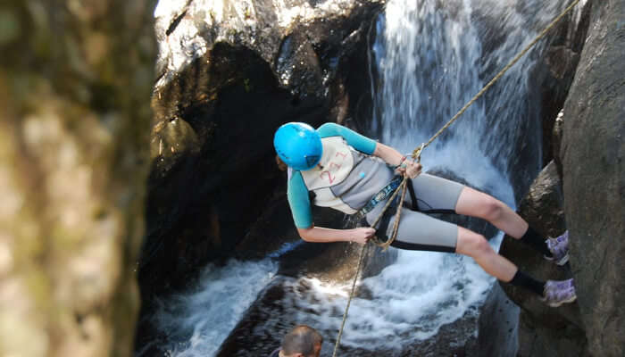 A girl enjoying waterfall rappelling